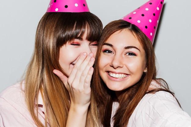 Selbstporträt von zwei frauen in rosa papiergeburtstagshüten. freunde tragen rosa pyjama. verspielte stimmung.
