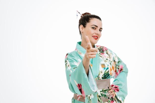 Selbstzufriedene frau im traditionellen japanischen kimono zeigt glücklich mit dem zeigefinger auf weiß