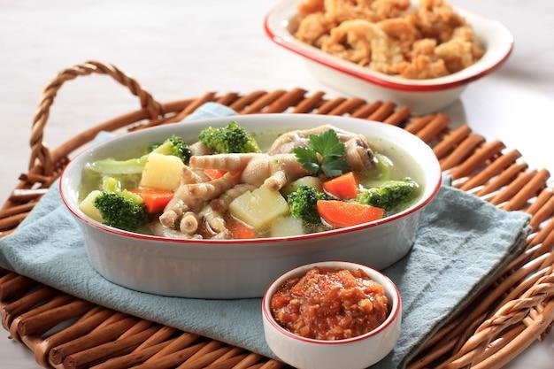 Selected focus chicken feet (ceker) auf klarer gemüsesuppe mit kartoffeln, brokkoli und karotten. serviert auf holztisch in ovaler schüssel mit sambal. und austernpilz-kopienraum für text