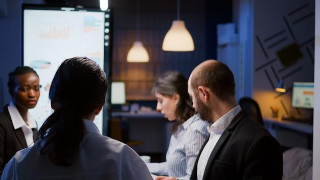 Selektive fokus-workaholics konzentrierten sich auf multiethnische geschäftsleute, die im besprechungsraum des unternehmensbüros überarbeiten, um spät in der nacht ideen zu sammeln. kollegen, die am schreibtisch sitzen und statistikpapiere analysieren