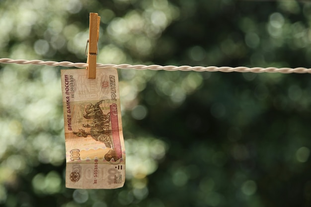 Selektive fokusaufnahme einer banknote, die mit einer wäscheklammer an einem draht hängt