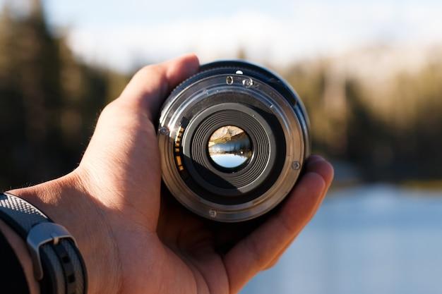 Selektive fokusaufnahme einer person, die ein kameraobjektiv hält