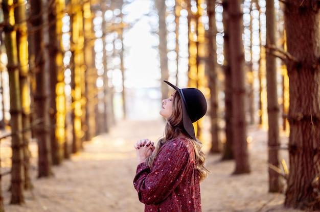 Selektive fokusaufnahme einer schönen jungen dame, die in einem wald betet