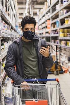 Selektive fokusaufnahme eines jungen mannes in einer maske, die untersucht, was zu kaufen ist - konzept der neuen normalität