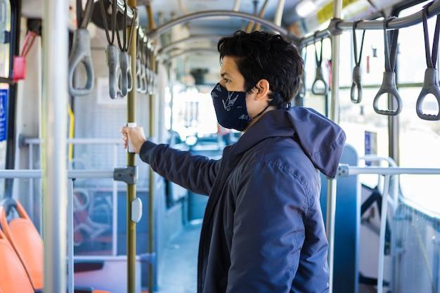 Selektive fokusaufnahme eines jungen mannes mit einer maske, die sich am geländer festhält