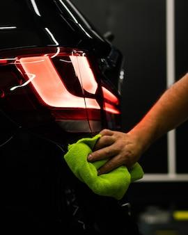 Selektive fokusaufnahme eines mannes, der den hinteren scheinwerfer eines autos mit einem mikrofasertuch reinigt