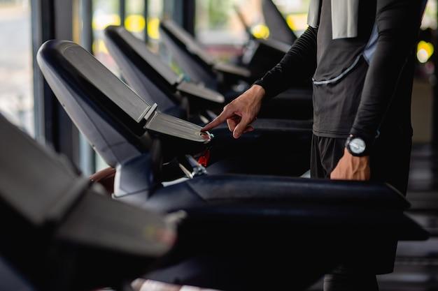 Selektive fokushand des jungen mannes, der sportbekleidung und smartwatch trägt und das programm auf dem laufband zum training im modernen fitnessstudio einstellt,
