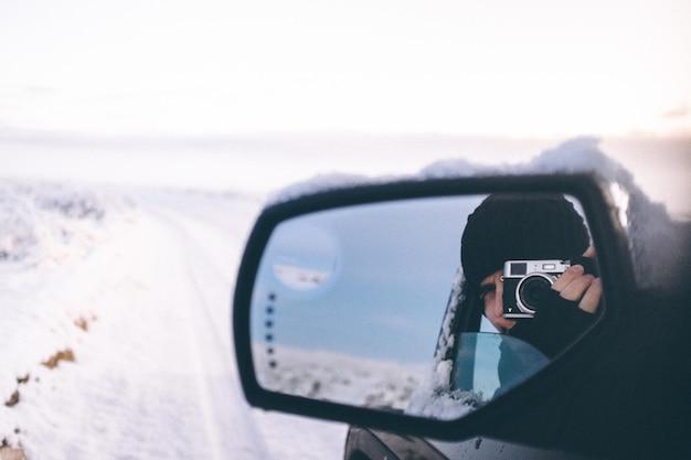 Selektive nahaufnahme einer person mit handschuhen und hut, die eine fotokamera hält