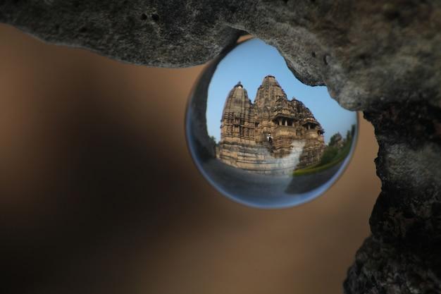 Selektive nahaufnahmeaufnahme der reflexion des tempels in orcha, indien in der glaskugel, die von einem felsen hängt