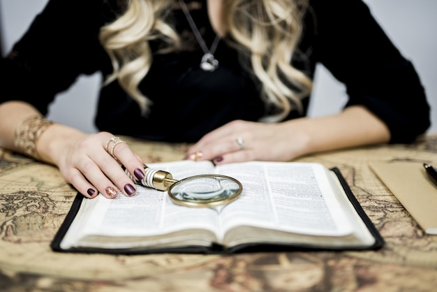 Selektive nahaufnahmeaufnahme einer person, die ein buch mit einer lupe liest