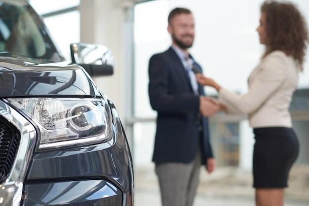 Selektiver fokus auf auto und glücklichem paar auf unschärfehintergrund.