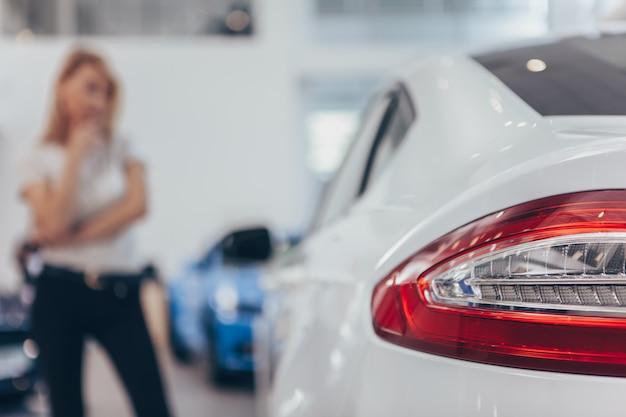 Selektiver fokus auf autolichtern eines automobils am weiblichen kunden der verkaufsstelle, der auto wählt