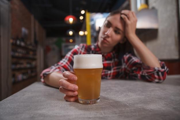 Selektiver fokus auf bierglas in der hand einer traurigen frau an der bar