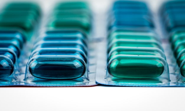 Selektiver fokus auf blaue und grüne weichgel-kapselpillen in blisterpackung
