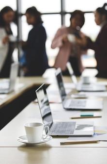 Selektiver fokus auf den schreibtisch, eine gruppe nicht erkennbarer geschäftsfrauen, die zur bruchzeit im büro zusammenstehen. die teamarbeit der weiblichen angestellten, die mit sich entspannt, im unschärfehintergrund.