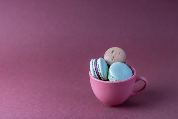 Selektiver fokus auf die macarons in der tasse auf rosa hintergrund