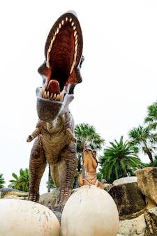 Selektiver fokus auf die reißzähne große braune dinosauriermutter und -kind im ei im stuckzoo