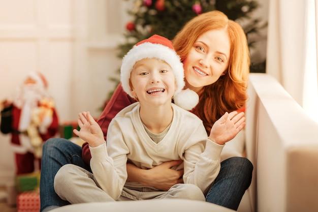 Selektiver fokus auf ein äußerst glückliches kind, das aufgeregt wird, während es neben seiner liebenden mutter sitzt und ihn auf einem sofa umarmt.