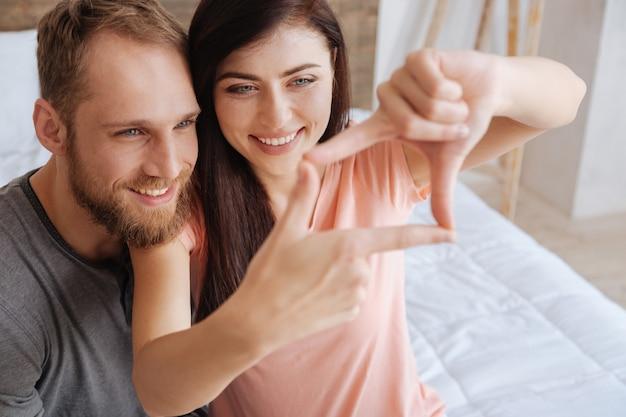 Selektiver fokus auf ein grauäugiges paar, das selbstporträtbilder mit den händen macht und gemeinsam freizeit genießt
