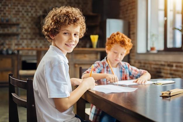 Selektiver fokus auf ein jugendliches kind mit haselnussbraunen augen, das in die kamera lächelt, während es mit bleistiften zeichnet und einige zeit mit einem jüngeren bruder verbringt.