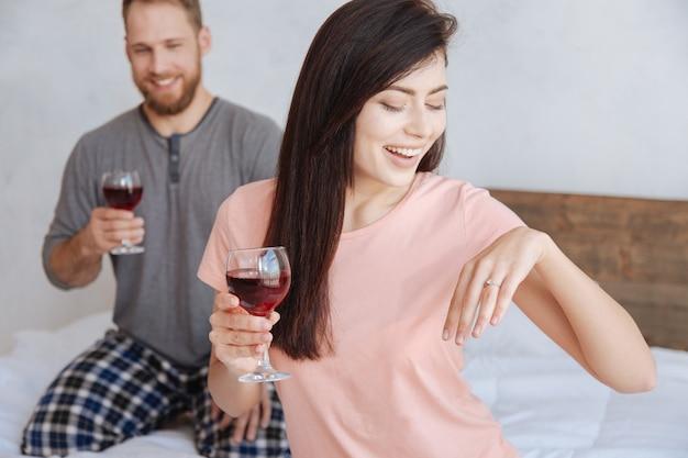 Selektiver fokus auf eine verlobte, die ihren diamantring genau beobachtet, während sie mit ihrem verlobten auf einem bett sitzt und den moment mit einem glas rotwein feiert