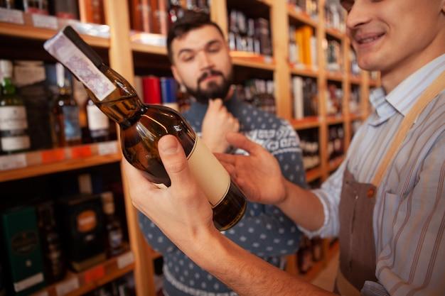 Selektiver fokus auf eine weinflasche in den händen eines winzers im gespräch mit einem kunden. hübscher mann, der leckeren alternden wein am supermarkt kauft