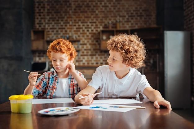 Selektiver fokus auf einen älteren jungen, der ein weißes hemd trägt und seinen lustigen jüngeren bruder verzieht, während er einen malpinsel hält und sein neues meisterwerk abbildet.