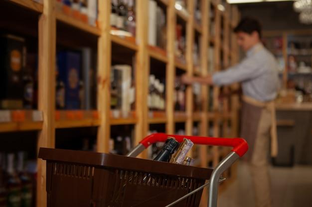 Selektiver fokus auf einen einkaufswagen mit flaschen, weinladenbesitzer organisiert getränke in den regalen