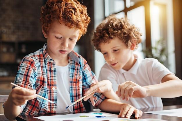 Selektiver fokus auf einen entzückenden rothaarigen jungen, der ein stück papier betrachtet, während er auf seinen älteren bruder wartet, der ihm beim malen zu hause hilft.