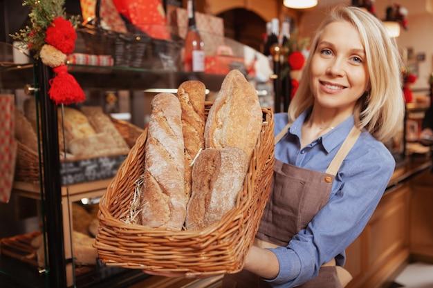 Selektiver fokus auf frische brotlaibe in einem korb, den eine glückliche bäckerin hält. köstliches food-konzept