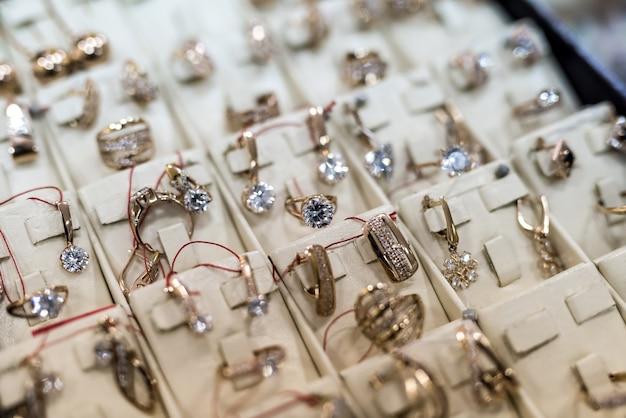 Selektiver fokus auf goldene ohrringe mit ring auf vitrine