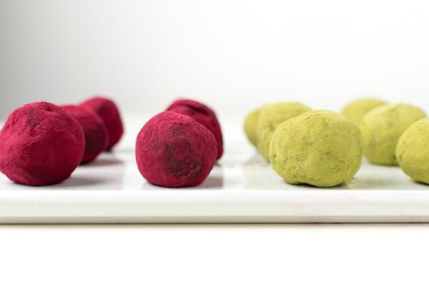 Selektiver fokus auf grünem tee matcha und rosa himbeerrüben-trüffeln
