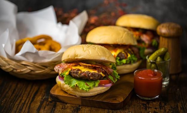 Selektiver fokus auf hamburger mit rindfleischburger, gebratenen zwiebeln, spinat, ketchup, pfeffer und käse serviert beilagen auf einem holzbrett mit erfrischungsgetränk.