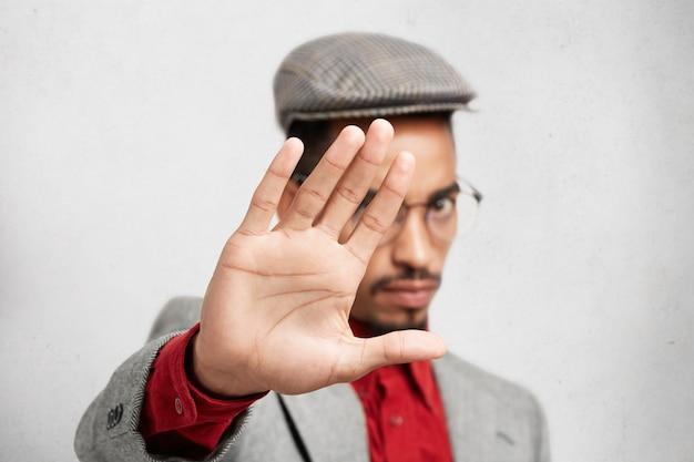 Selektiver fokus auf handfläche. strenger mischling in runder brille, zeigt stoppschild mit der hand