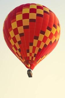 Selektiver fokus auf heißluftballon, der in kappadokien über das tal fliegt. heißluftballons sind eine traditionelle touristische attraktion in kappadokien.