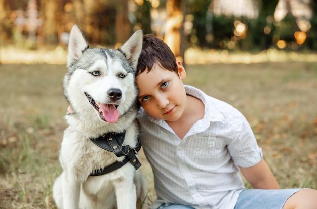 Selektiver fokus auf husky-hund. verschwommenes glückliches kind, das welpen kuschelt