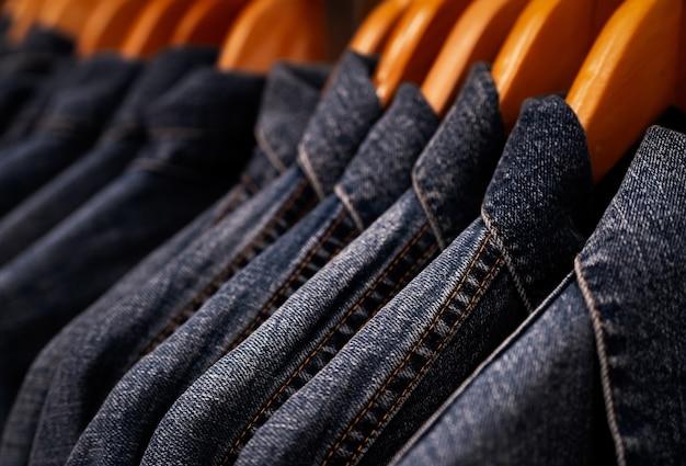 Selektiver fokus auf jackenjeans, die im kleidergeschäft am gestell hängen. jeans mit jeansmuster.