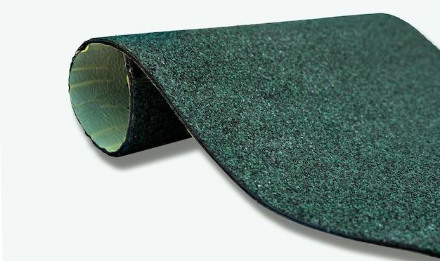 Selektiver fokus auf jägergrünes schindeldach auf weißer oberfläche. dachmaterial. schindeldach textur. schindeldach aus asphalt, kunststofffaser. raue dunkelgrüne granulatoberfläche.