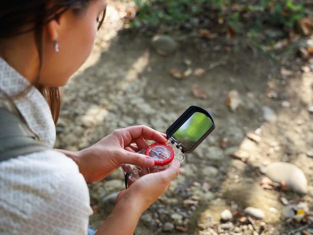 Selektiver fokus auf kompass in händen der touristenfrau, um die richtung der bewegung zu bestimmen