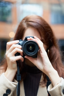 Selektiver fokus auf linse. schönes stilvolles modernes mädchen hält kamera in ihren händen und macht fotos.