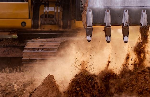 Selektiver fokus auf metallschaufelzähne von baggerladergrabboden. baggerlader arbeitet durch graben von erde auf der baustelle. raupenbagger, der auf boden gräbt. erdbewegungsmaschine. aushubfahrzeug.