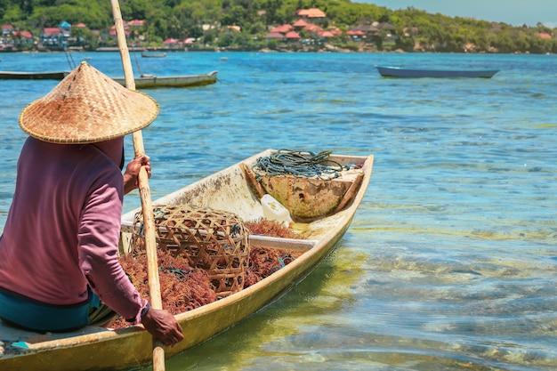 Selektiver fokus auf seetang auf einem fischerboot aus holz, das zum meer fährt