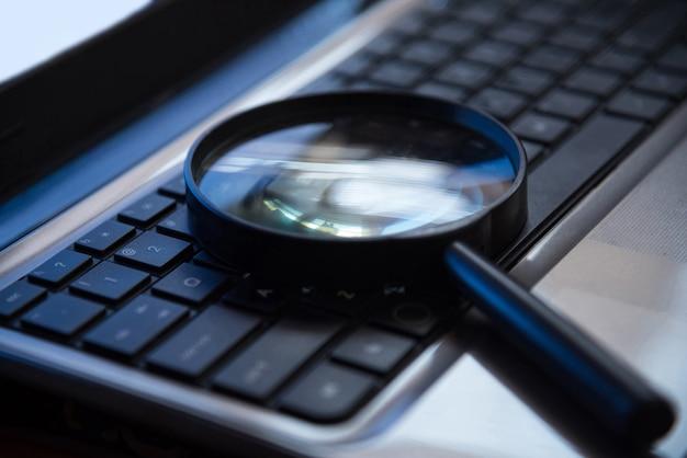 Selektiver fokus auf tastatur mit dem vergrößerungsglas, das konzept sucht