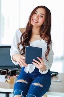 Selektiver fokus auf telefon, weiblicher vlogger, influencer oder online-verkäufer, der einen tablet-computer hält, und blick auf die kamera, die bereit ist, ein kosmetisches überprüfungsvideo aufzunehmen. online-marketing-konzept.