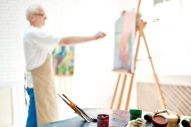 Selektiver fokus auf vordergrund mit palette von farben und pinseln für das mischen von farben, die auf tabelle liegen.