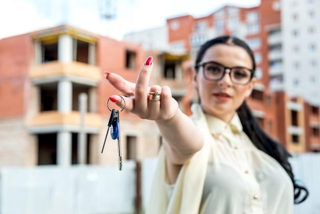 Selektiver fokus auf weibliche hand mit schlüsseln aus neuer wohnung