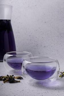 Selektiver fokus, blauer blumentee mit trockenen blüten, in klaren tassen mit doppelglas