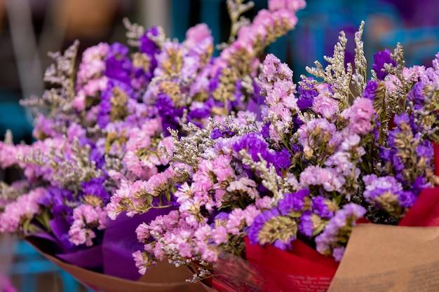 Selektiver fokus, bündel des schönen blumenblumenstraußes im markt, heller gemischter bunter blumenblumenstrauß im weinlesepapier im blumengeschäft