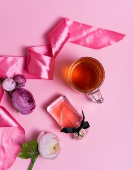 Selektiver fokus: ceylon-schwarztee in einer transparenten tasse auf einem rosa tisch mit einem rosa satinband. frauenparfüm und blumen.