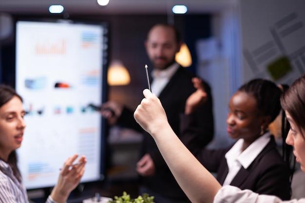 Selektiver fokus der geschäftsfrau leder, die am schreibtisch sitzt und die marketing-präsentation analysiert und die papierkram über finanzielle graps diskutiert. vielfältige multiethnische teamarbeit brainstorming-projektideen in meeti